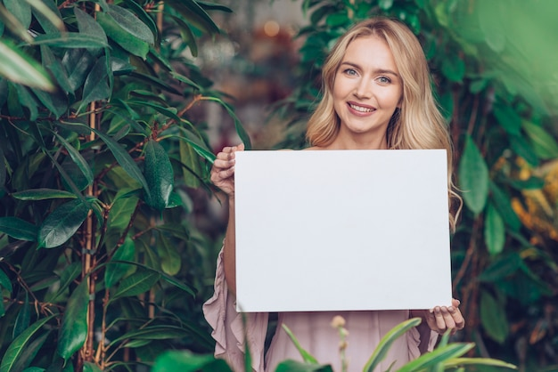 Portrait of a smiling blonde young woman standing in plant nursery showing white blank placard