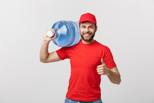 Портрет улыбающегося в бутылках с доставкой воды курьером в красной майке и кепке