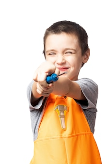 Portrait of a smiling boy carpenter in orange work overalls, posing, holding a screwdriver and pointing to the camera, having fun on a white isolated background. children's costume for a holiday