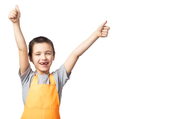 Portrait of smiling boy carpenter in orange work overalls posing, holding, thumbs up