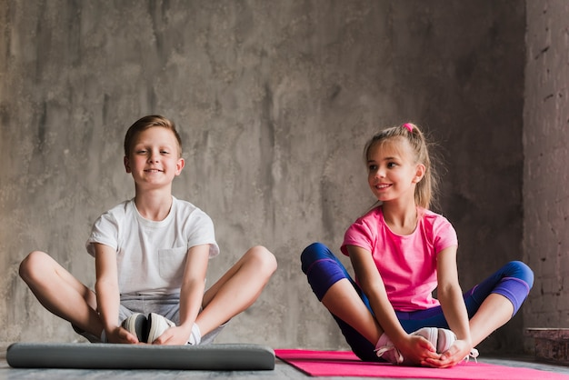 Portrait of a smiling boy and girl sitting together exercising against concrete backdrop