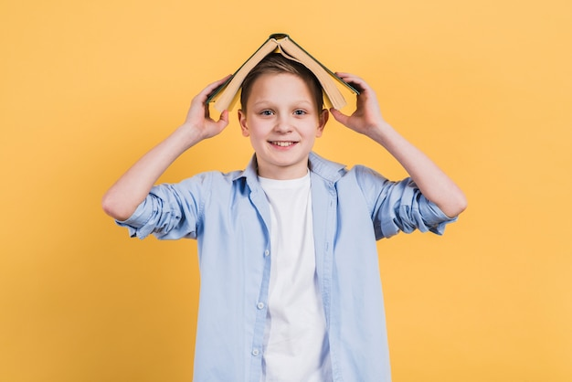 Portrait of a smiling boy holding book over his head looking to camera against yellow background