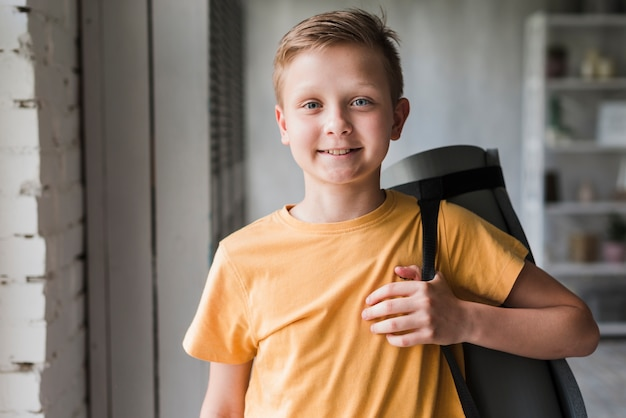 Portrait of a smiling boy holding exercise mat on his shoulder