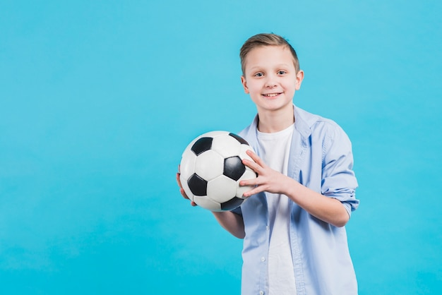 Portrait of a smiling boy holding soccer ball in hand standing against blue sky