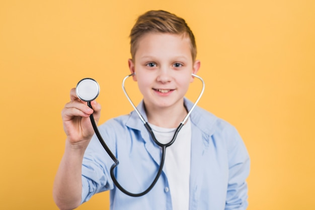 Portrait of a smiling boy holding stethoscope towards camera standing against yellow background