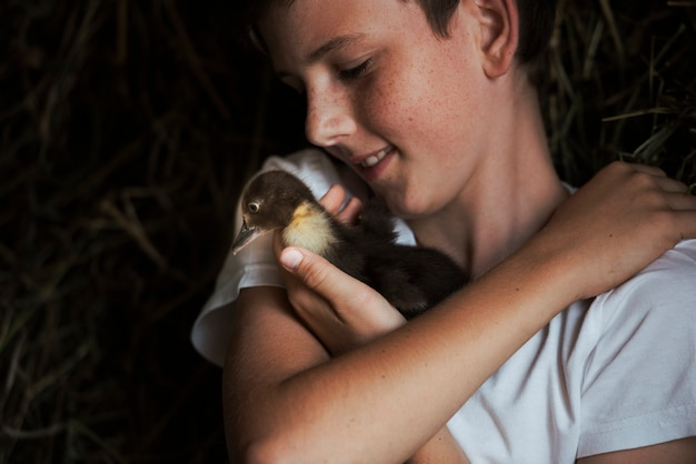 Portrait of a smiling boy loving his duckling