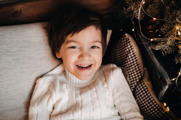 Portrait of a smiling boy lying at the christmas tree at home.