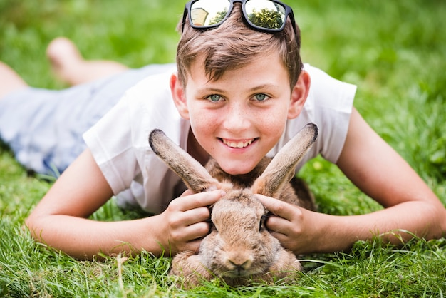 Portrait of smiling boy lying over rabbit on green grass in the park