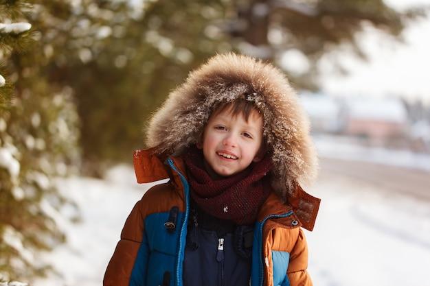 Portrait of smiling boy in a snowy forest in winter