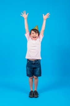 Portrait of smiling boy wearing party hat with arm raised in blue backdrop