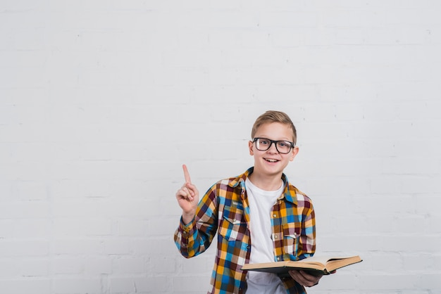 Portrait of a smiling boy with eyeglasses holding an open book in hand pointing his finger upward