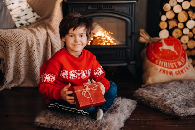 Portrait of a smiling boy with a gift in his hands near the fireplace at home