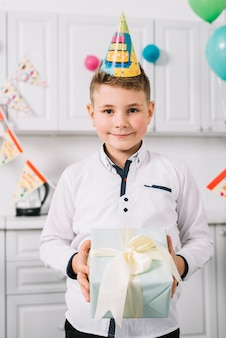 Portrait of a smiling boy with party hat on his head holding wrapped present box
