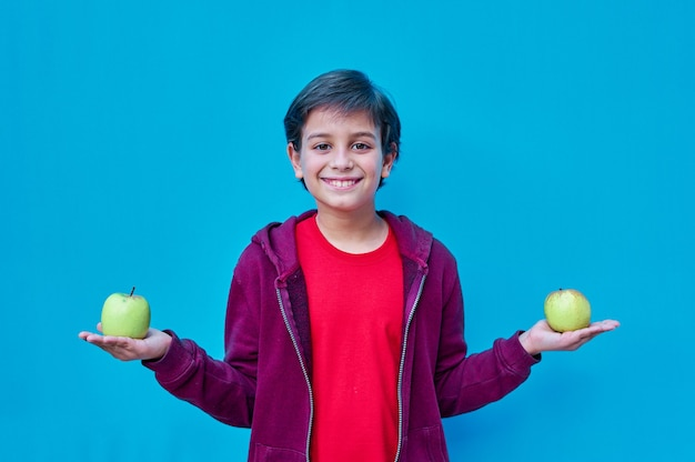 A portrait of smiling boy with red shirt holding an apple in each hand