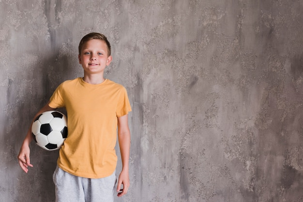 Portrait of a smiling boy with soccer ball standing in front of concrete wall