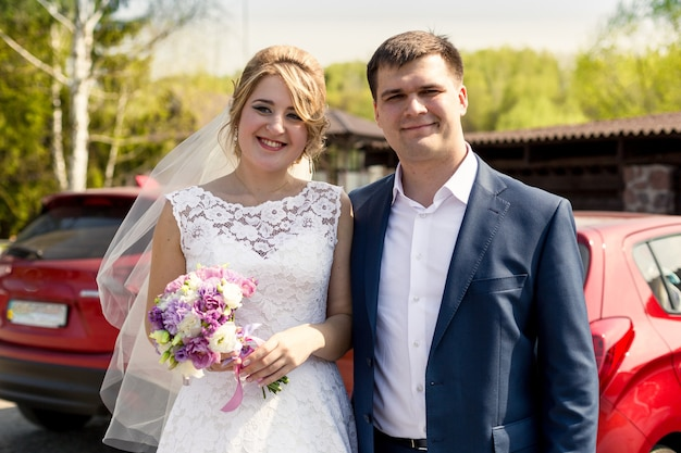 Portrait of smiling bride and groom posing at sunny day at park