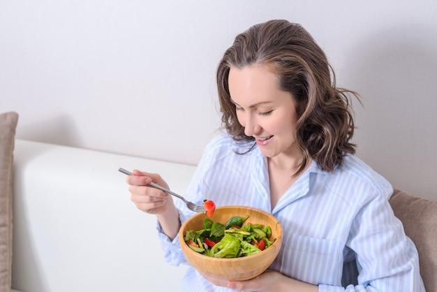 Portrait of smiling brunette eating fresh vegetable, vegetarian salad.