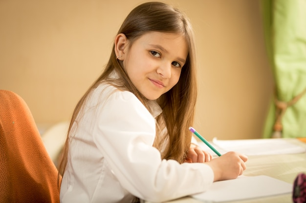 Portrait of smiling brunette girl in white shirt sitting behind desk and doing homework