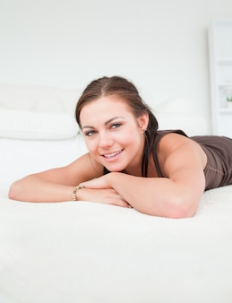 Portrait of a smiling brunette liying on a carpet