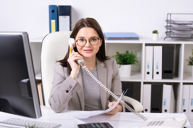 Portrait of smiling brunette secretary sitting at desk and answering phone call in office