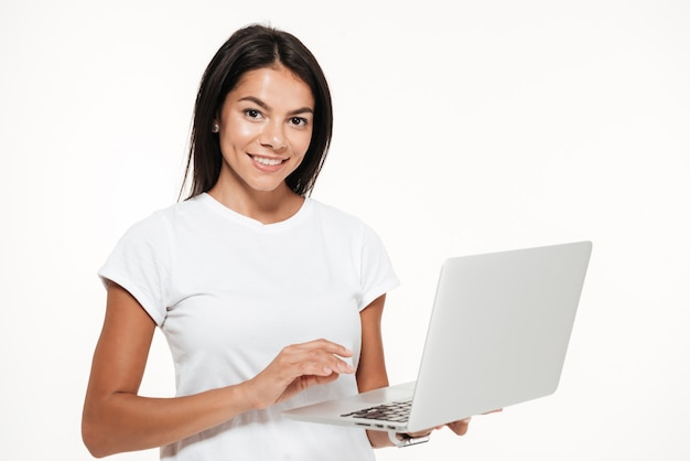 Portrait of a smiling brunette woman holding laptop computer