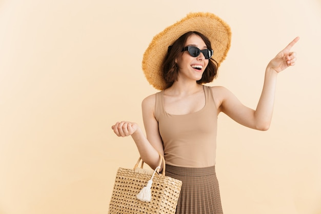 Portrait of smiling brunette woman wearing straw hat and sunglasses posing with summer bag while pointing finger at copyspace isolated