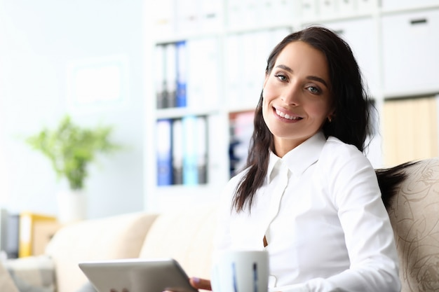 Portrait of smiling brunette working with tablet and sitting on sofa. cheerful woman wearing white blouse and looking at camera with happiness. business concept