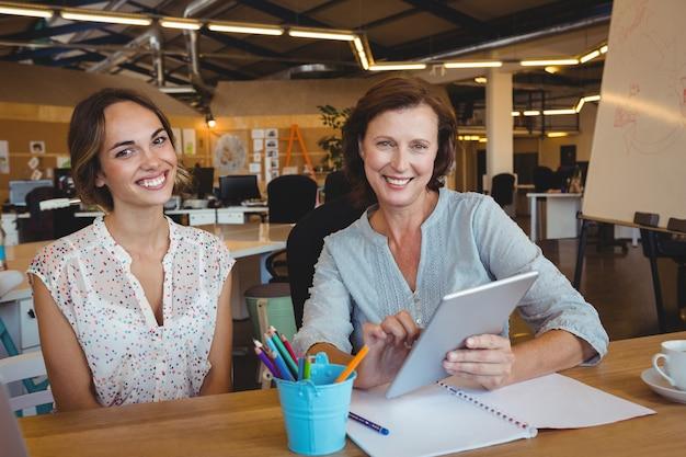 Portrait of smiling business executives holding digital tablet