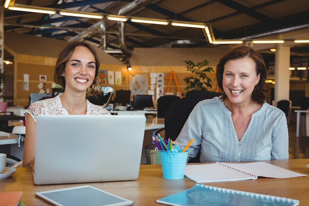 Portrait of smiling business executives sitting at desk