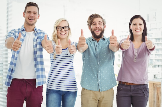 Portrait of smiling business people with thumbs up while standing at office