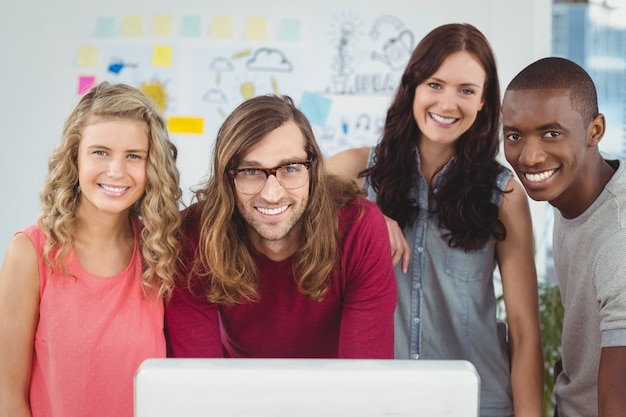 Portrait of smiling business team standing at computer desk