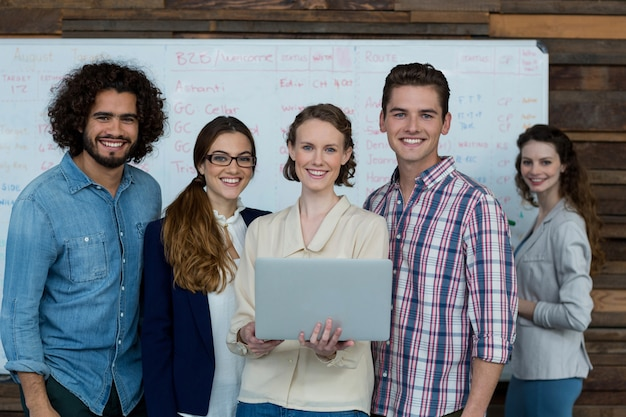 Portrait of smiling business team using laptop