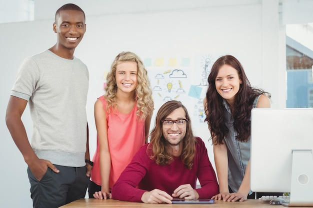 Portrait of smiling business team working at computer desk