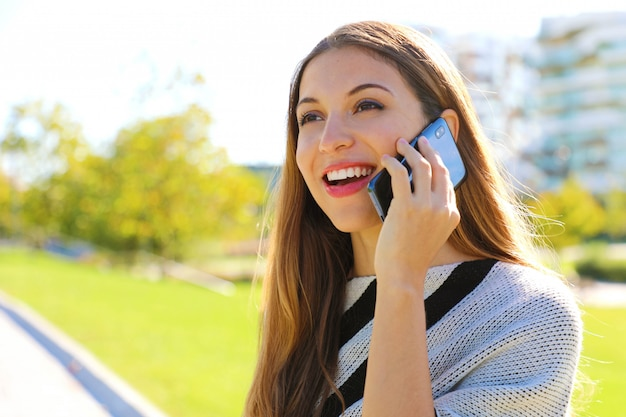 Portrait of smiling business woman having a conversation on her cell phone outdoors.