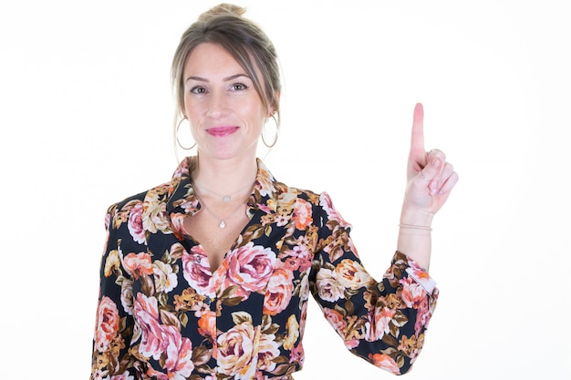 Portrait of smiling business woman pointing finger aside white empty copyspace