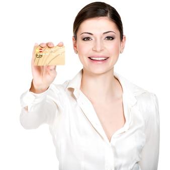 Il ritratto della donna sorridente di affari in una camicia bianca tiene la carta di credito - isolata su bianco.