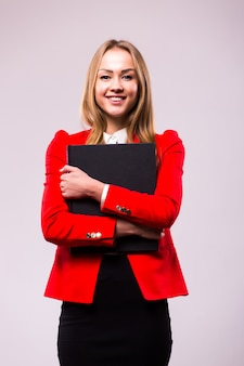 Portrait of smiling business woman with red folder, isolated on white wall