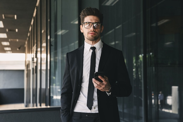Portrait of smiling businessman dressed in formal suit standing outside glass building, and holding mobile phone