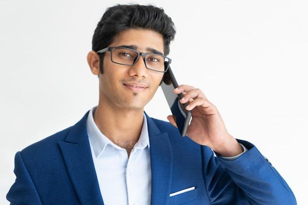 Portrait of smiling businessman in glasses talking on smartphone.