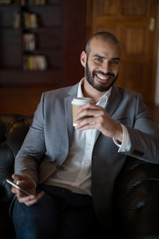 Portrait of smiling businessman holding mobile phone and coffee cup in waiting area