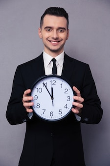 Portrait of a smiling businessman holding wall clock over gray wall