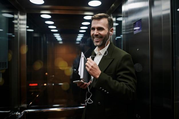 Ritratto di uomo d'affari sorridente che ascolta musica in ascensore