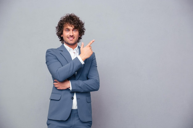 Portrait of a smiling businessman pointing finger away over gray wall and looking at front