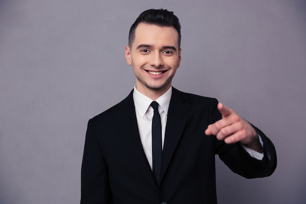 Portrait of a smiling businessman pointing finger over gray wall