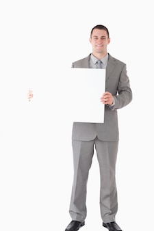 Portrait of a smiling businessman showing a blank panel