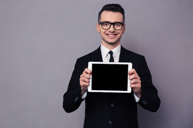Portrait of a smiling businessman showing blank tablet computer screen over gray wall