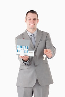 Portrait of a smiling businessman showing a miniature house and