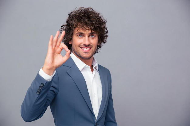 Portrait of a smiling businessman showing ok sign over gray wall
