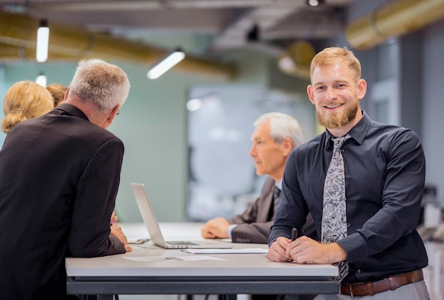 Portrait of smiling businessman standing while team discussing in the background