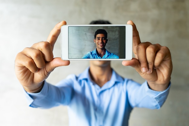 Portrait of smiling businessman taking selfie with smartphone.